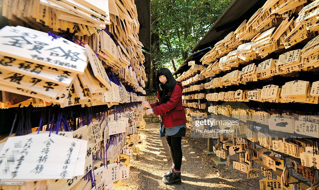 A high school student tries to hang a wooden plaque at Kitano Tenmangu Shrine on January 8, 2013 in Kyoto, Japan. 100,000 plaques are hung at the shrine, honours Michizane Sugawara as god. The entrance examination season begins as the National Center Test takes place on January 19.