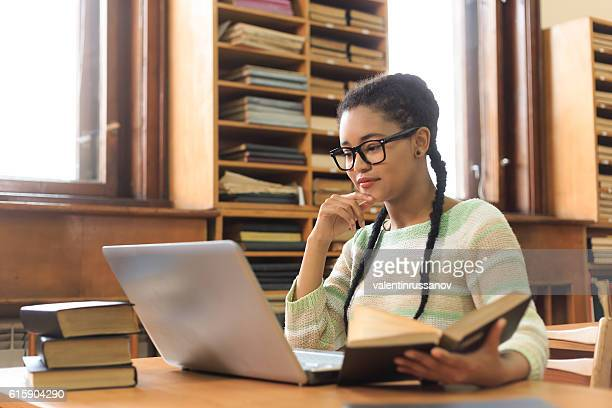 High school student using laptop at library