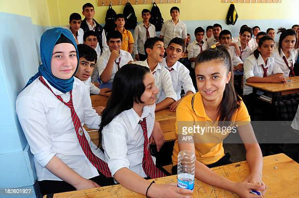A high school student weraing a headscarf poses on October 1 2013 with her classmates in a Diyarbakir school Turkey's prime minister Recep Tayyip...