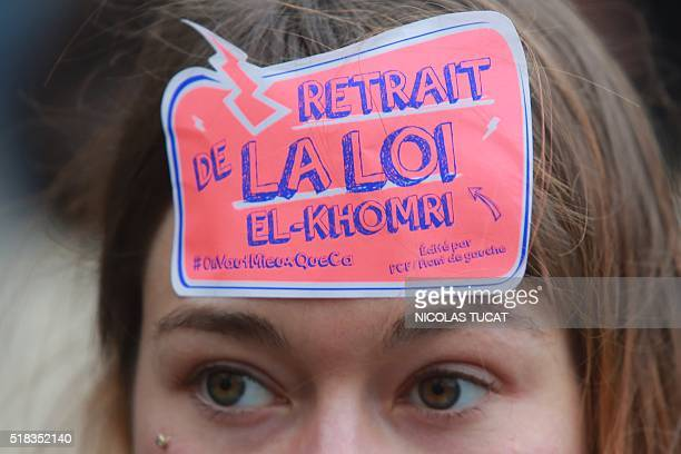 A high school student with a sticker reading 'Withdraw of the El Khomri law' marches during a demonstration against the French government's planned...