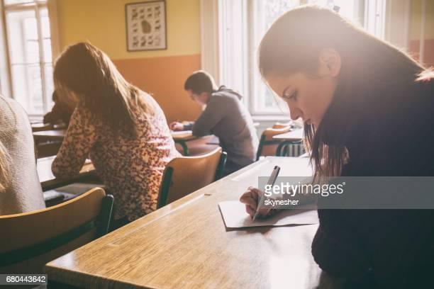 Lycéen écrit sur un morceau de papier dans la salle de classe.