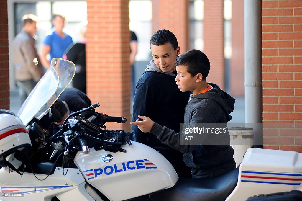 High school students from sensitive neighbourhood (le Mirail, Bellefontaine, Bagatelle, Empalot) of the southwestern French city of Toulouse, look at a police motorbike parked at the central police station of Toulouse on October 5, 2012, as part of the French homeland security days.