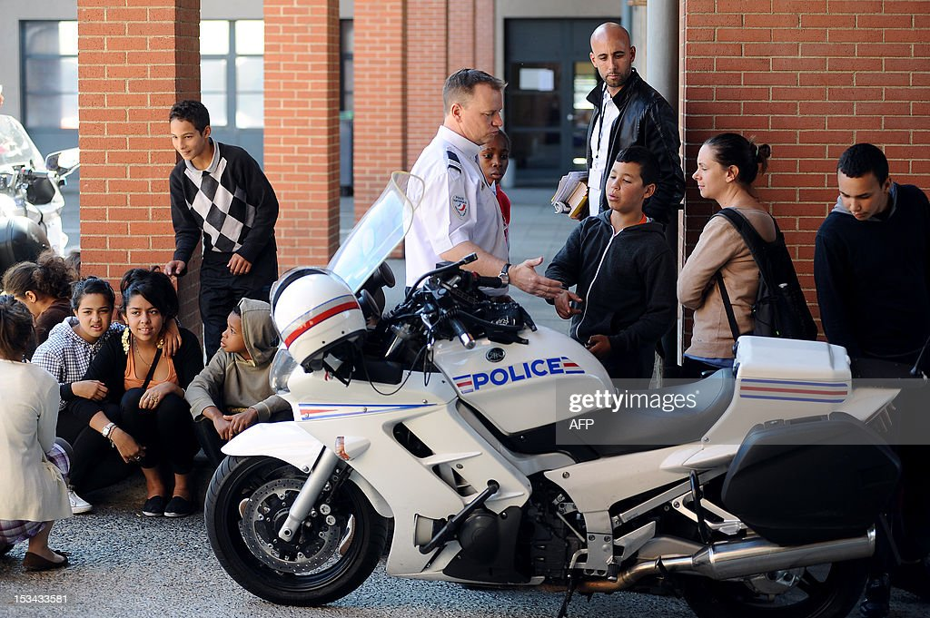 High school students from sensitive neighbourhood (le Mirail, Bellefontaine, Bagatelle, Empalot) of the southwestern French city of Toulouse, speak with a police officer at the central police station of Toulouse on October 5, 2012, as part of the French homeland security days.