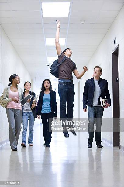 High school students in school corridor watching friend jumping