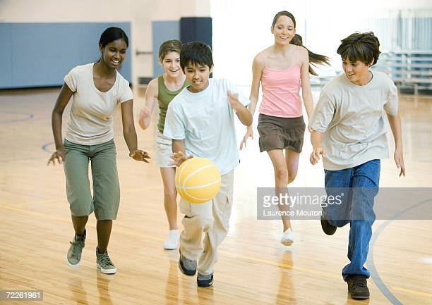 High school students playing basketball in school gym