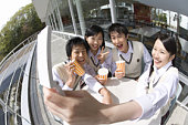 High school students smiling and photographing with mobile phone, fish-eye lens