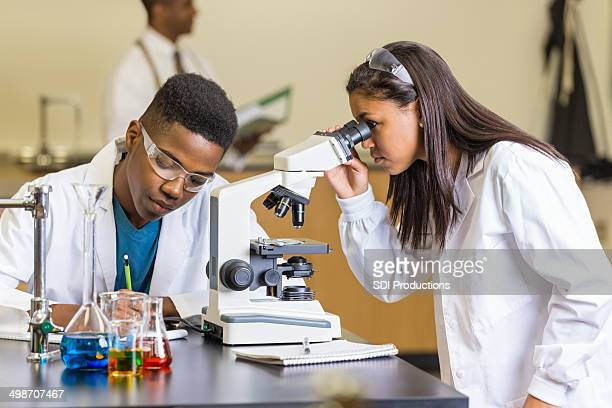High school students using microscope, examining slides in science class