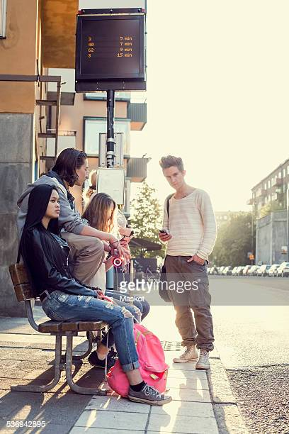 High school students waiting at bus stop