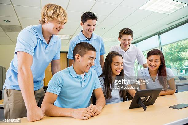 High school students wearing uniforms, working with technology in class