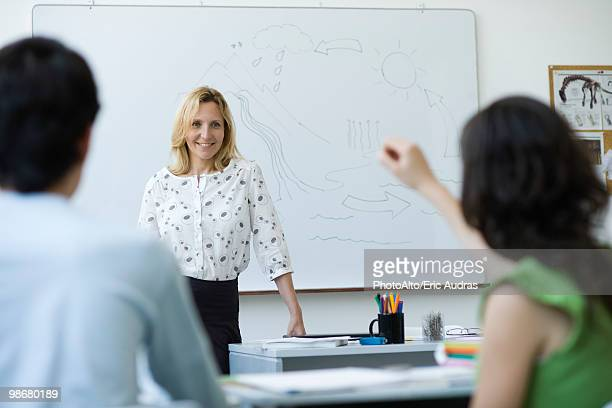High school teacher standing in front of class, answering question