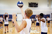 High School Volleyball Match In Gymnasium Holding Ball