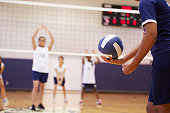 High School Volleyball Match In Gymnasium With Ball
