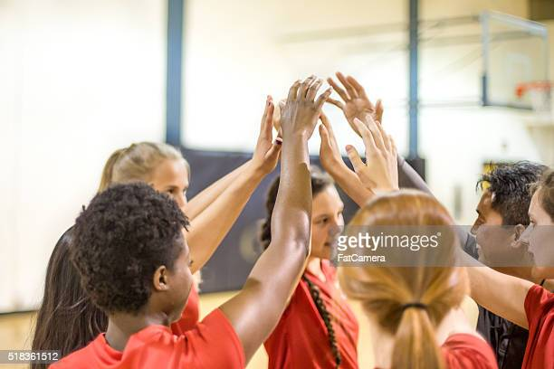 High school volleyball players in team huddle