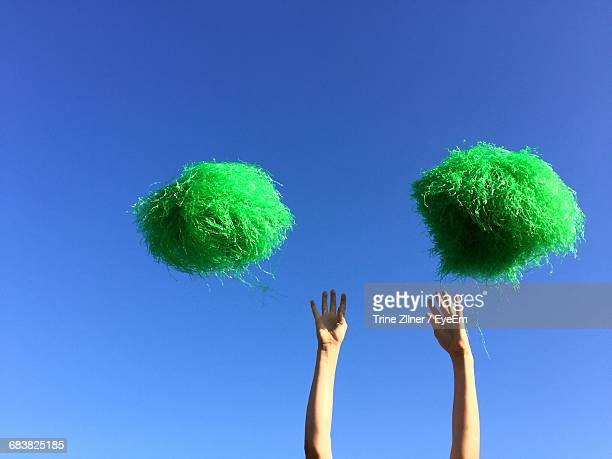 High Section Of Cheerleader And Pom Poms