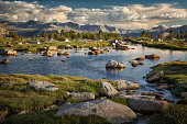 High Sierra lake with rocks, mountains and clouds