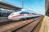 High speed white train on the railway station at sunset. Nuremberg, Germany. Modern intercity train on the railway platform. Industrial. Amazing passenger train on railroad. Transportation. Europe
