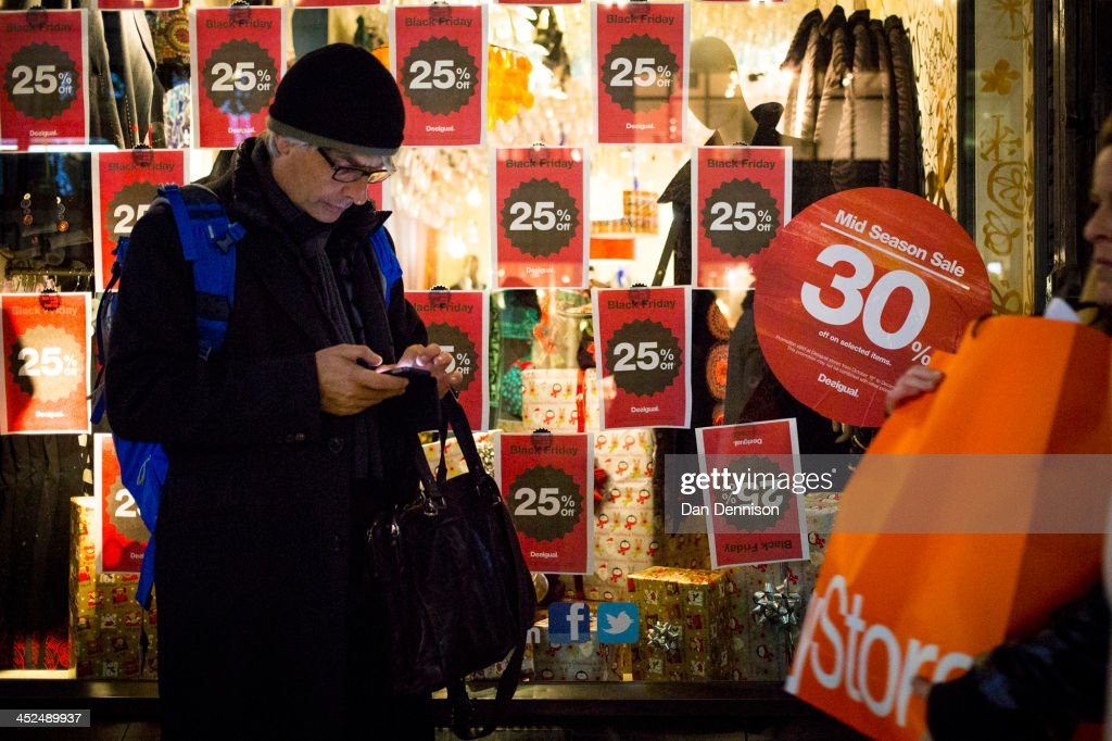 A high street shopper stands outside a clothing chain offering a pre-Christmas sale on November 29, 2013 in London, United Kingdom. Though traditionally a US phenomenon, 'Black friday' sales appear to have taken hold in the UK with many retailers offering large discounts for one day only, mimicking the behaviour of their American counterparts.