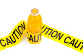 """""""Sugary sport drink bottle wrapped in yellow caution tape, dietary warning of high sugar drink, isolated on white background, copy space"""""""