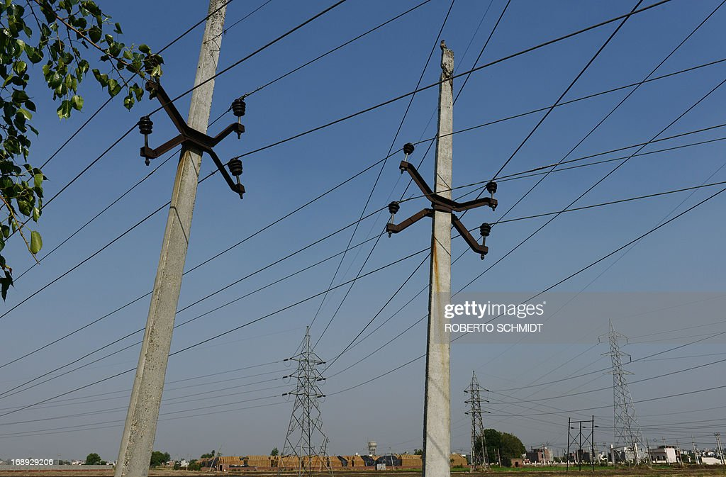 High voltage lines criss cross over a field near an electricity sub station in the northwestern Indian city of Amritsar on May 16, 2013. India, which has one of the largest integrated electricity grids in the world is challenged by peak electricity demands from consumers in the summer months of June and July when the temperatures hover at around 48 Degrees Celcius.