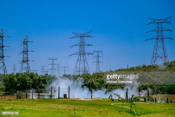 A High voltage power line next to a geothermal pool with steam in the KenGen or Kenya General Energy Olkaria geothermal power station area in Hells´s...