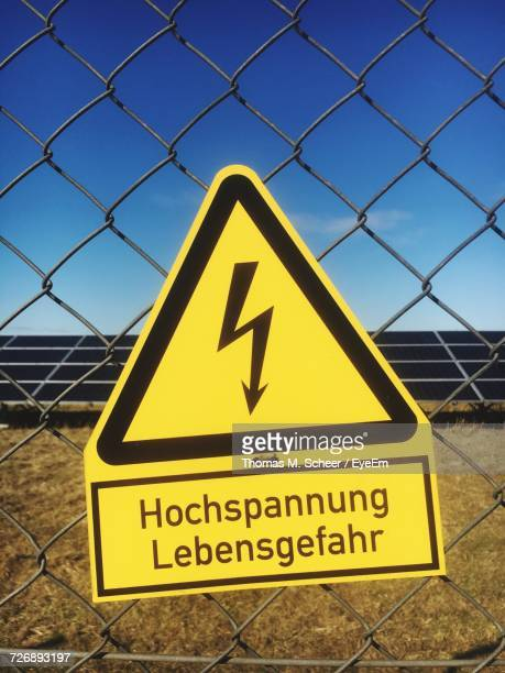 High Voltage Sign On Chainlink Fence Against Solar Panels On Field