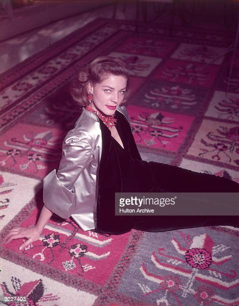 Highangle portrait of American actor Lauren Bacall wearing a coral necklace and earrings and a gold satin jacket over a black velvet body suit seated...
