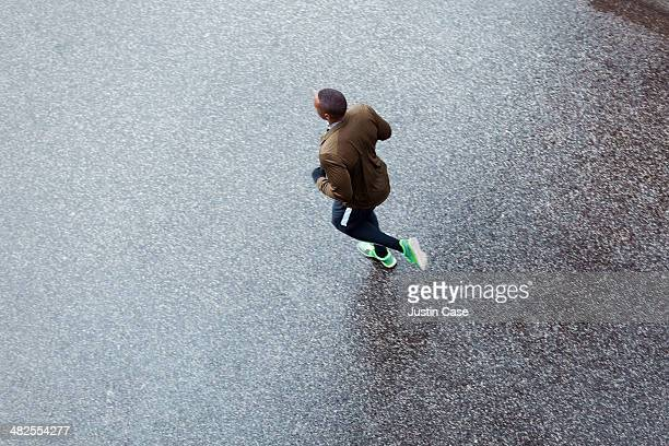 High-angle shot of a men jogging on a wet street