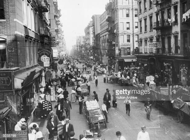 Highangle view people shopping in the open market on Delancey Street Lower East Side New York City Pushcarts line both sides of the street