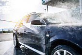 High-pressure washing car outdoors. Car washing under the open sky.