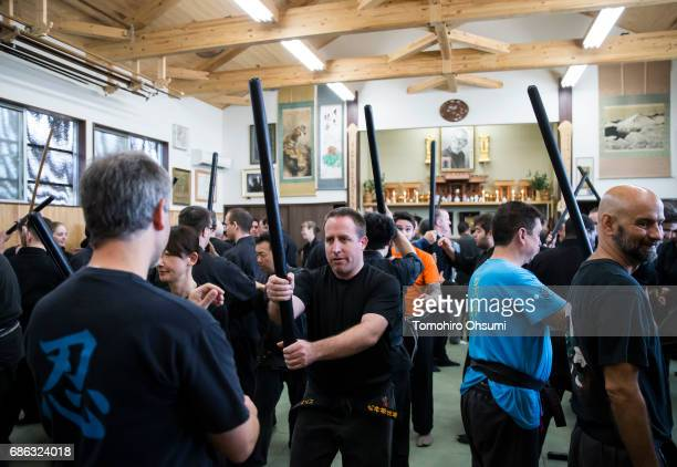 Highranked disciples of Grandmaster Masaaki Hatsumi use rods as they take part in a lesson at the Bujinkan dojo on May 21 2017 in Noda Japan The...