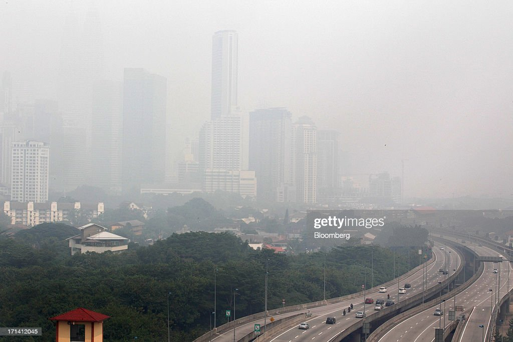 High-rise buildings stand shrouded in smog in Kuala Lumpur, Malaysia, on Monday, June 24, 2013. Malaysia called for a meeting of Southeast Asian ministers as early as next week after haze from illegal Indonesian forest fires reached hazardous levels in parts of the region. Photographer: Goh Seng Chong/Bloomberg via Getty Images
