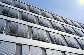 Facade of modern high-rise office building with covered windows Venetian blinds against blue sky