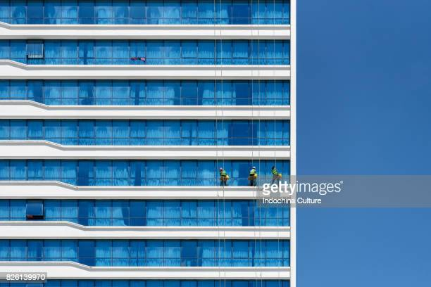 High-rise window cleaners hanging on the building