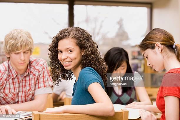 High-escolar Menina sorridente na biblioteca