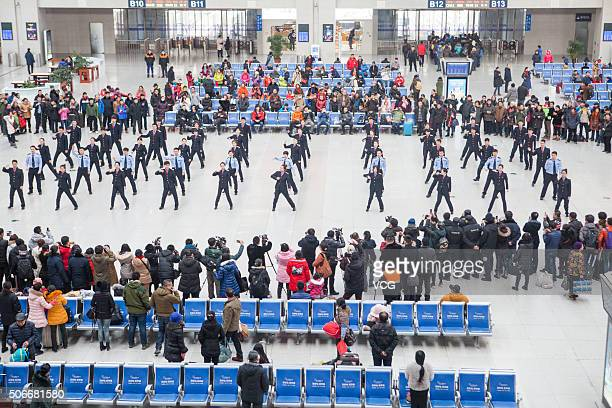 Highspeed rail attendants perform during a flash mob at the waiting hall of the railway station on January 24 2016 in Changchun Jilin Province of...