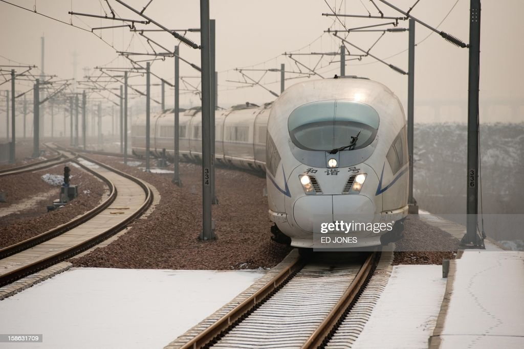 A high-speed train arrives at a platform in Hebei province south of Beijing on December 22, 2012. China showed off the final link of the world's longest high-speed rail route, set to open on December 26, stretching from Beijing to the southern Chinese city of Guangzhou. Travelling at around 300 kph, trains on the new route are expected to cover the 2,298-kilometre (1,425-mile) journey in a third of the current time from 22 hours to eight. AFP PHOTO / Ed Jones