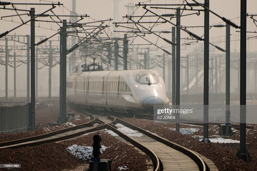 A high-speed train departs a platform in Hebei province south of Beijing on December 22, 2012. China showed off the final link of the world's longest high-speed rail route, set to open on December 26, stretching from Beijing to the southern Chinese city of Guangzhou. Travelling at around 300 kph, trains on the new route are expected to cover the 2,298-kilometre (1,425-mile) journey in a third of the current time from 22 hours to eight. AFP PHOTO / Ed Jones