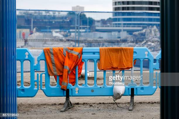 A highvisibility jacket and sandbag sit on fencing as demolition work takes place at the Nine Elms Square construction site in London UK on Tuesday...