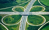 "An elevated view of a clover leaf shaped highway interchange. This is the ""Feuchtwangen, Crailsheim"" interchange of A7 (vertical), North - South, and A6 (horizontal), East - West highways in Southern"