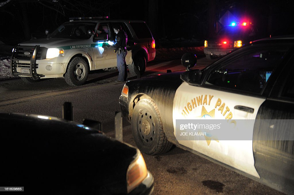 A highway patrol officer checks with colleagues at a roadblockon on Highway 38 near Angeles Oaks during a standoff with fugitive ex-cop Christopher Dorner, near San Bernardino, California on February 12, 2013. Nobody has yet been found in a burnt-out US mountain cabin where Dorner was believed to have barricaded himself after a six-day manhunt, a police spokesman said. Media reports that a body had been found in the cabin near Big Bear, east of Los Angeles, and identified as Dorner's were false, said Los Angeles Police Department (LAPD) spokesman Andrew Smith.