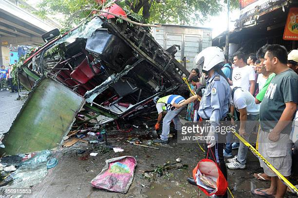 A highway patrol officer collects belonging of passengers of the bus that fell from an elevated highway in Manila on December 16 2013 Twentytwo...