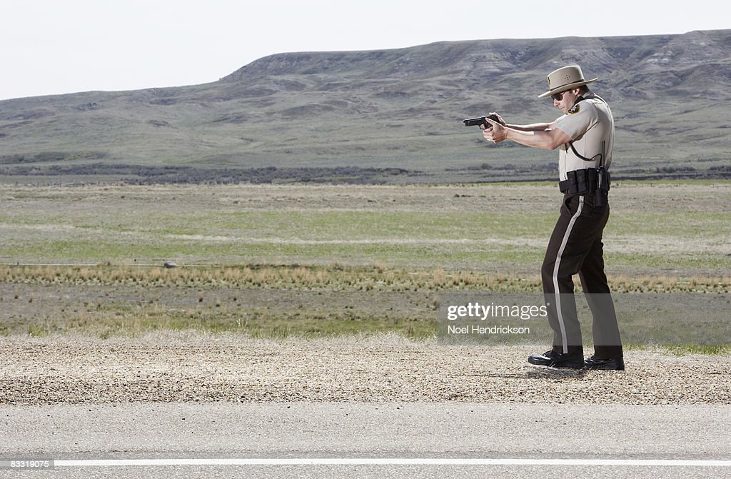 highway patrolman pointing gun : Stock Photo
