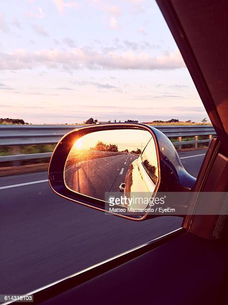 Highway Reflection In Side-View Mirror Of Car Against Sky
