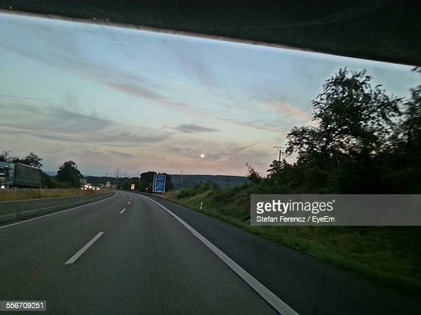 Highway Seen Through Car Windshield During Sunset