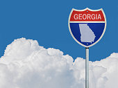 Highway sign for Interstate road in Georgia with map in front of clouds