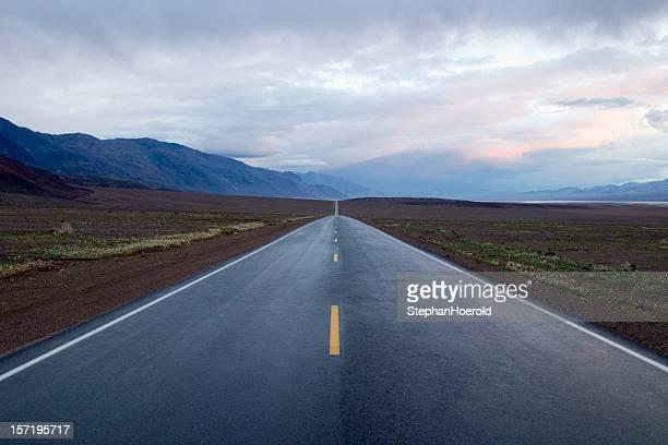 Highway zum Infinity: Scheinbar endlose Straße unter Dramatischer Himmel