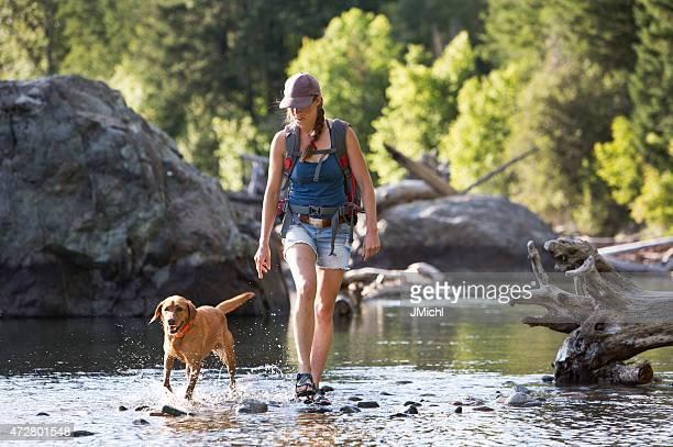 Randonneur et chien traversant la partie peu profonde de la rivière.