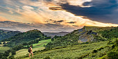 Senior male hiker looking at sunset panorama of Castell Dinas Bran near Llangollen from Panorama Walk