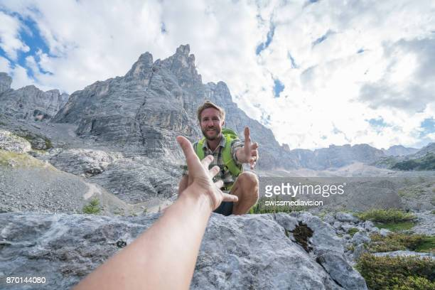 Hiker assists teammate on mountain trail, Dolomites, Italy
