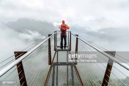Hiker at lookout in a rainy foggy day
